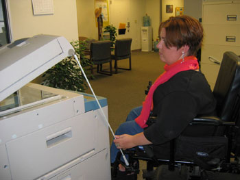 A wheelchair rider to raises the lid of a copy machine with a push rod.